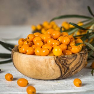 Sea buckthorn berries with leaves on wooden background. Healthy vitamin autumn berries.
